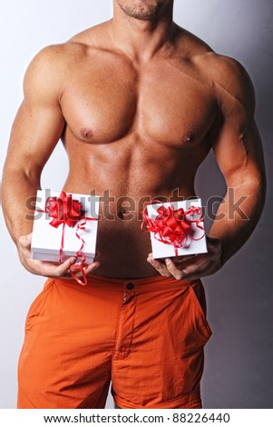 Image of muscular bodybuilder holding xmas gifts, isolated on grey