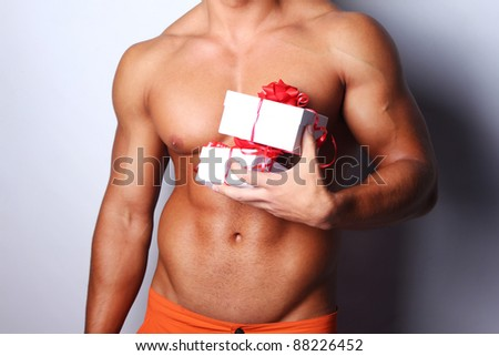 Image of muscular man holding xmas gifts, isolated on grey