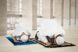 Image of Muslim man with his son posing prostration while praying in the mosque