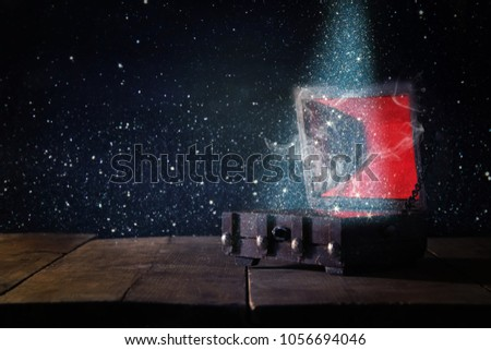 Image of mysterious treasure chest with glitter light and smoke over wooden old table #1056694046