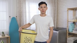image of nice asian chinese guy confident smiling at camera, holding laundry basket and hand in pants pocket while standing in bright house.
