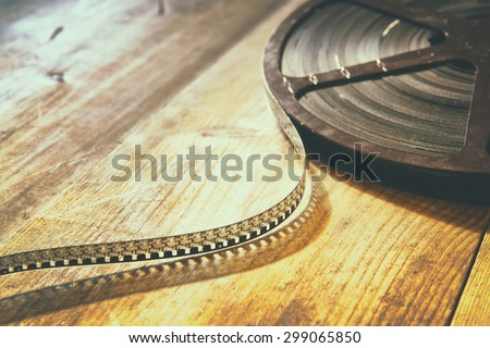 image of old 8 mm movie reel over wooden background. retro style image