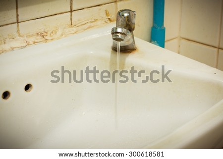 image of old sink with damaged water tap .