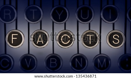 "Image of old typewriter keyboard with scratched chrome keys that spell out the word ""FACTS"". Lighting and focus are centered on ""FACTS""."