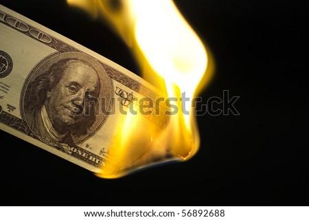 Image of one hundred bill burning on black background