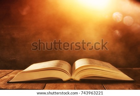 image of open antique book on wooden table with glitter background #743963221
