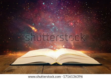 image of open antique book on wooden table with glitter overlay