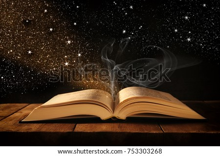 image of open antique book on wooden table with glitter overlay Foto stock ©