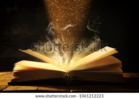 image of open antique book over wooden table