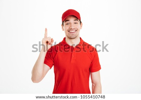 Image of optimistic delivery man in red t-shirt and cap smiling and pointing finger upward on copyspace text or product isolated over white background