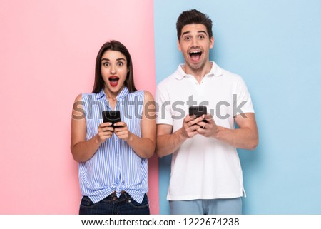 Image of optimistic man and woman in casual wear holding mobile phones isolated over colorful background #1222674238