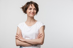 Image of optimistic woman in basic t-shirt smiling and looking aside while standing with arms crossed isolated over white background