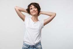 Image of optimistic woman in basic t-shirt touching her hair and looking aside isolated over white background