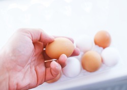 image of package of eggs and a male hand