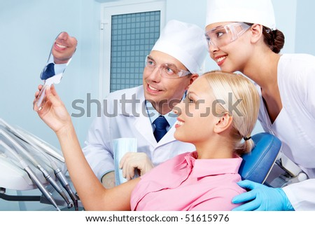 Image of patient holding mirror with doctor and assistant near by