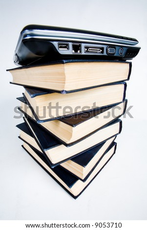 Image of pile of books with a black closed laptop on top