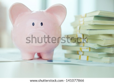 Image of pink piggy bank and stack of dollar bills