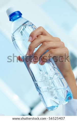 Image of plastic water bottle in female hand
