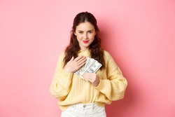 Image of pleased brunette woman holding money near chest, hugging dollar bills and looking coy at camera with confident smile, standing against pink background