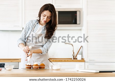 Image of pleased brunette woman wearing apron cooking muffins with cream in modern kitchen stock photo