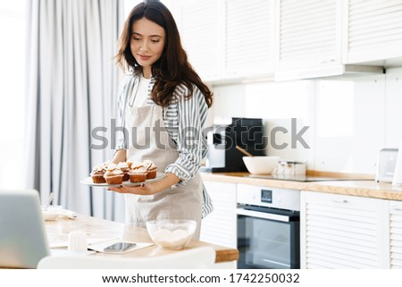Image of pleased brunette woman wearing apron smiling and holding muffins in modern kitchen stock photo