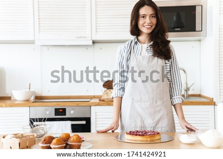 Image of pleased brunette woman wearing apron smiling while cooking pie in modern kitchen stock photo