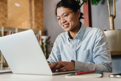 Image of pleased handsome asian man in eyeglasses smiling and studying with laptop while sitting at table