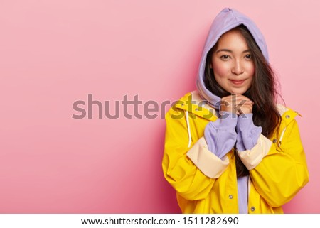 Image of pleased young brunette woman wears casual sweatshirt with hoody, yellow waterproof raincoat, keeps hands pressed together under chin, feels relaxed and calm, being cold after walking in rain