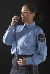Image of policewoman talking to her cb phone against black background