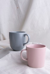 Image of Pottery, Dark grey and Pink pastel ceramic cups on the white cloth or vintage white look fabric background