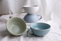 Image of Pottery, light Pastel ceramic cups on the white cloth or vintage white look fabric background