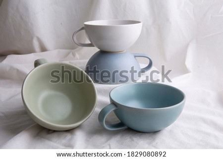 Image of Pottery, light Pastel ceramic cups on the white cloth or vintage white look fabric background Сток-фото ©