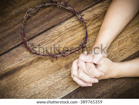 image of prayer  hands with  metal Barbed Wire made like the crown of thorns of Jesus on wooden background, Christian concept, Easter background with copy space Stock photo ©