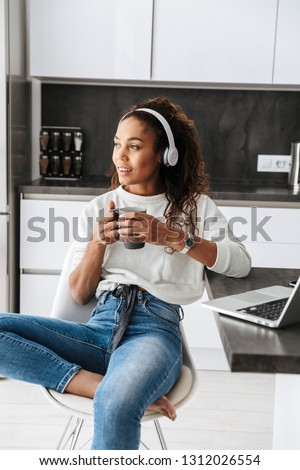 Image of pretty african american girl wearing headphones using laptop while sitting in bright kitchen