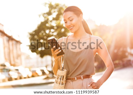 Image of pretty asian woman walking outdoors on the street using mobile phone.