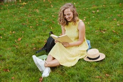 Image of pretty blonde woman smiling and reading book while sitting at grass in green park