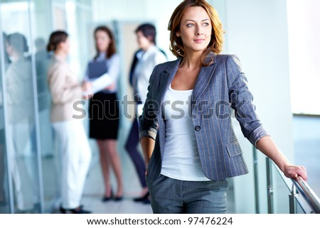 Image of pretty business leader with interacting partners at background