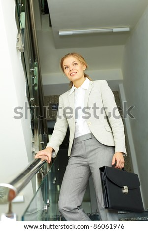 Image of pretty businesswoman with briefcase going down in office building
