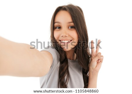 Image of pretty cute girl standing isolated over white wall background make selfie looking camera showing peace gesture.