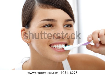 Image of pretty female brushing her teeth in the morning