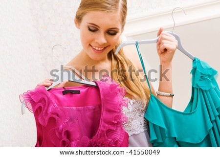 Image of pretty female looking at smart dresses while choosing a right one