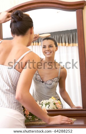 Image of pretty female looking in mirror while brushing hair