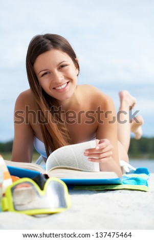 Image of pretty female lying on the beach and reading book