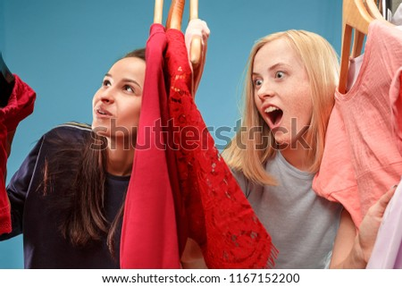Image of pretty females looking a dress while choosing it. Concept of shopping and lifestyle
