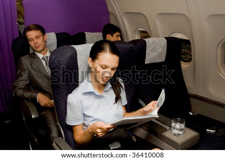 Image of pretty girl reading magazine in airplane with sleeping men behind