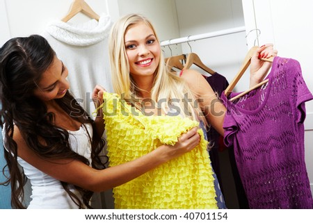 Image of pretty girl trying on smart dress on her friend