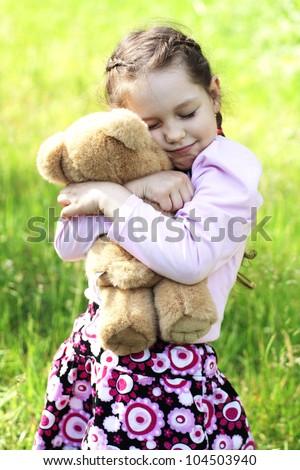 Image of pretty little girl hugging her teddy bear in park
