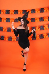 Image of pretty witch girl in black halloween costume holding champagne bottle and glass isolated over orange pumpkin wall