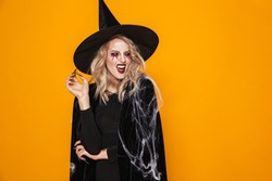 Image of pretty witch woman wearing black costume and halloween makeup smiling at camera isolated over yellow background