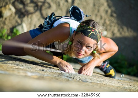 Image of pretty woman climbing on the rock